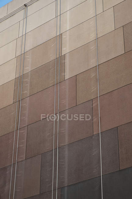 Long strips hanging over tiled wall of modern building on city street — Stock Photo