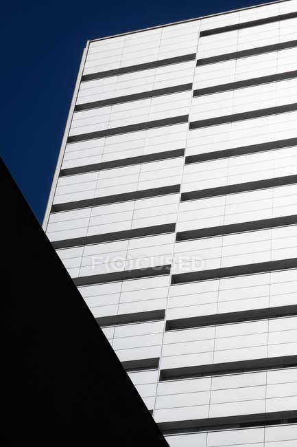 Wand eines zeitgenössischen Wolkenkratzers gegen wolkenlosen blauen Himmel an einem sonnigen Tag auf der Stadtstraße — Stockfoto