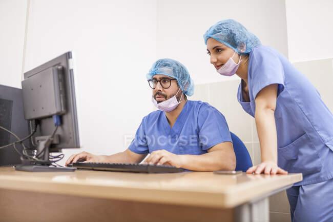 Équipe de chirurgiens, homme et femme utilisant l'ordinateur avant l'opération et commettant les détails — Photo de stock