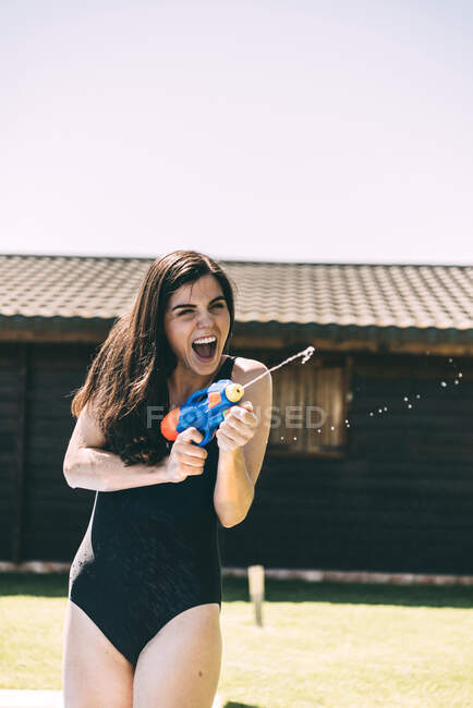Woman aiming with water-pistol — Stock Photo