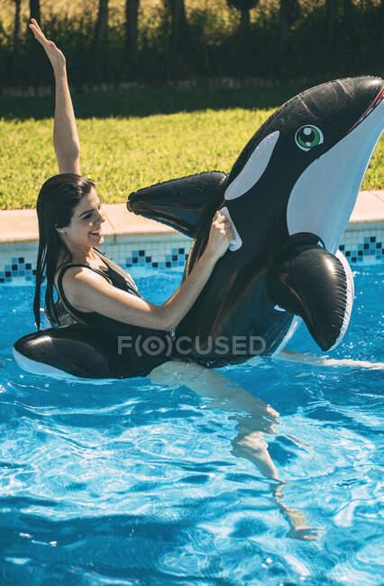 Mujer joven excitada divirtiéndose en la piscina con juguete inflable para peces en un día soleado. - foto de stock