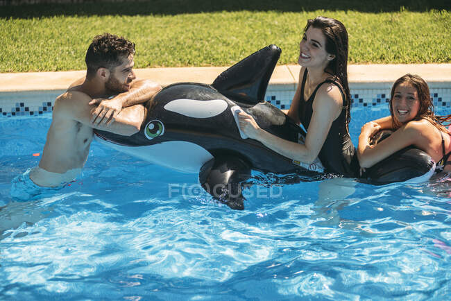 Happy friends with toy in pool — Stock Photo