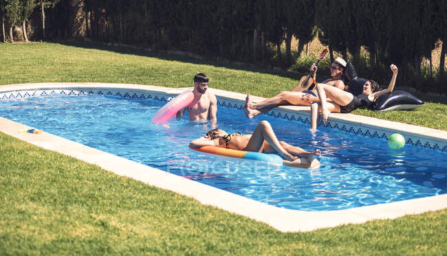Persone che si rilassano in piscina insieme — Foto stock