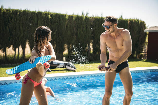 Young cheerful couple in swimsuits playing in pool — Stock Photo