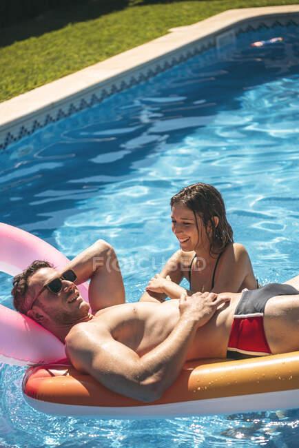 Мужчина и женщина отдыхают в бассейне — стоковое фото
