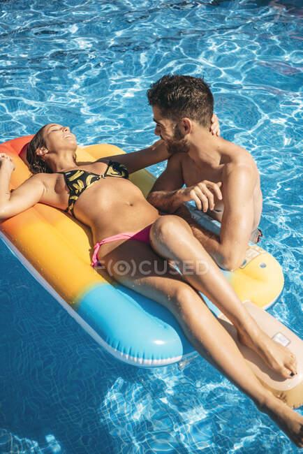 Молода пара відпочиває в басейні. — стокове фото