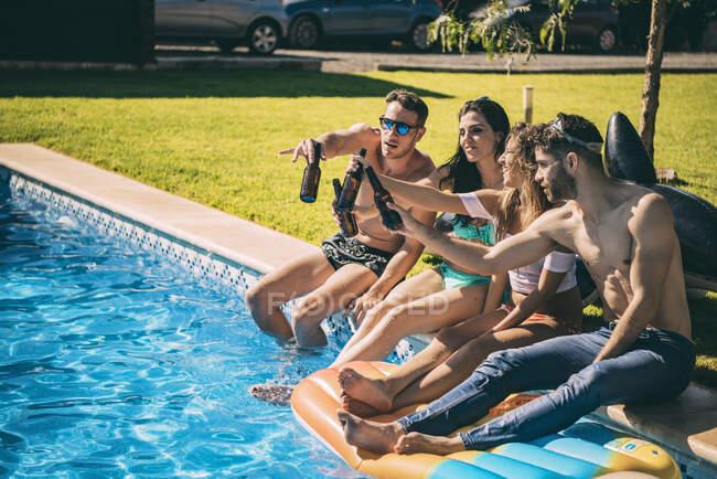 Amici che bevono birra a bordo piscina — Foto stock