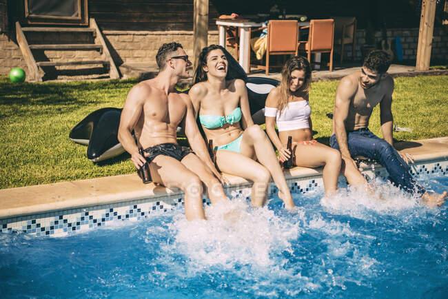 Amici seduti a bordo piscina e spruzzi con i piedi — Foto stock