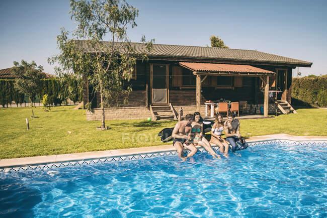 Giovani amici che bevono in piscina — Foto stock