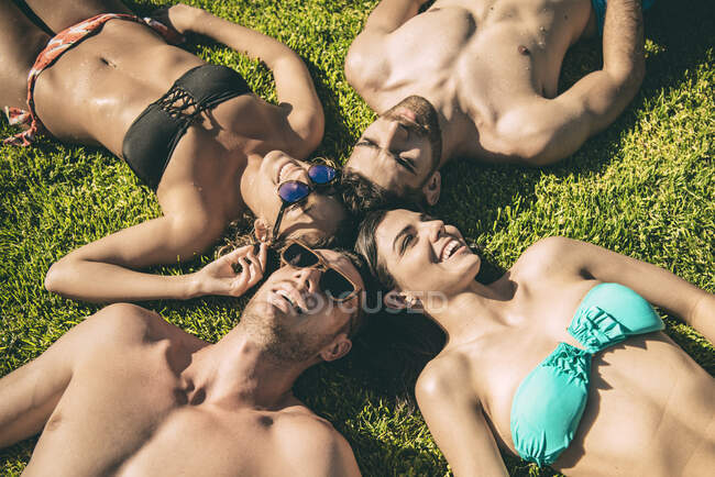 Amigos tumbados en la hierba mirando al cielo - foto de stock