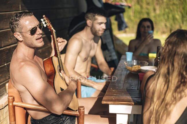 Друзі грають на гітарі на ганку. — стокове фото