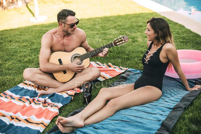 Tipo con guitarra tocando para su novia - foto de stock