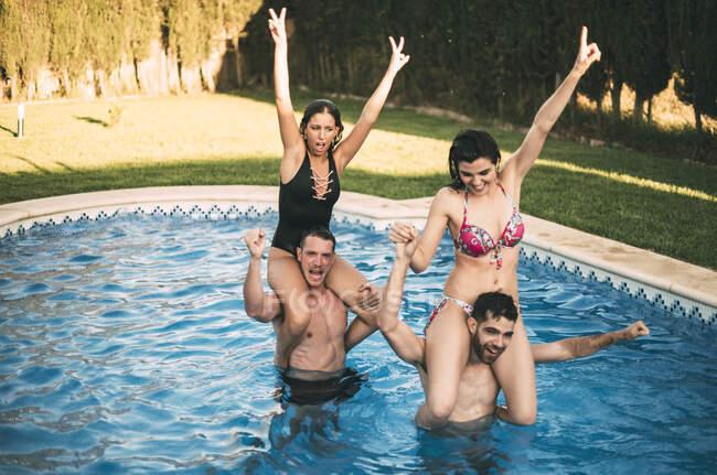 Ragazzi equitazione ragazze sul collo in piscina — Foto stock