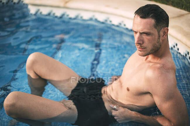 Людина лежить на сходинках у басейні. — стокове фото