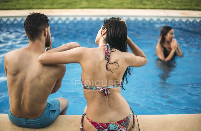 Друзі сидять на краю басейну. — стокове фото