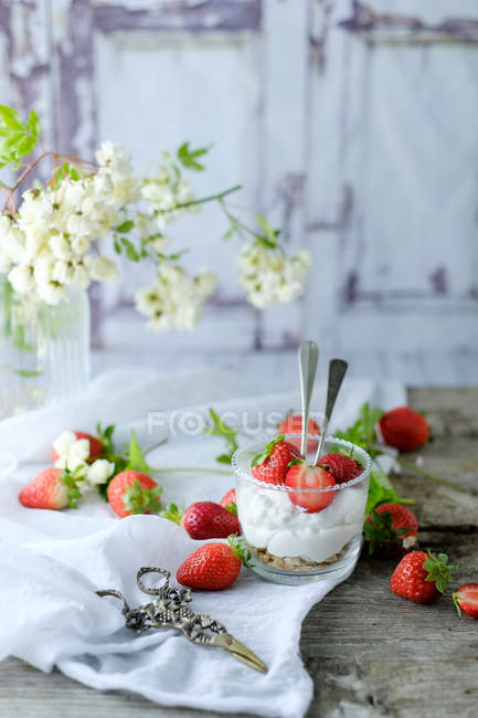 Creamy sweet dessert with fresh juicy strawberries served in glass on rustic wooden table — Stock Photo