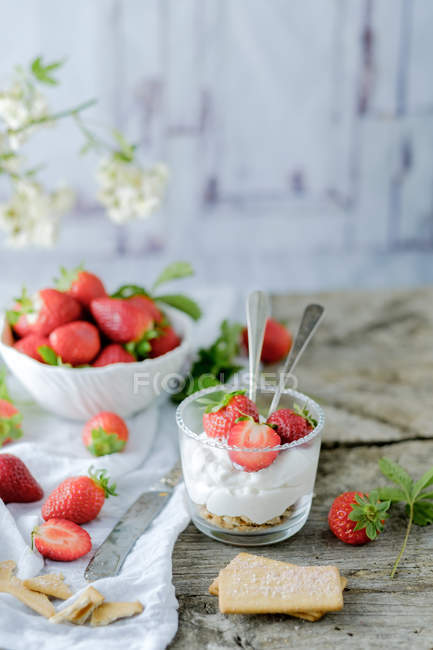Creamy sweet dessert with fresh juicy strawberries served in glass on rustic wooden table with biscuits — Stock Photo