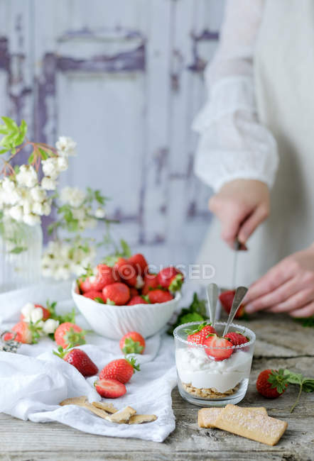 Creamy sweet dessert with fresh juicy strawberries served in glass on rustic wooden table with biscuits and female hand cutting berries on background — Stock Photo