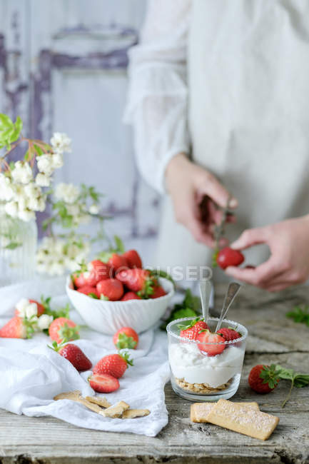 Creamy sweet dessert with fresh juicy strawberries served in glass on rustic wooden table with biscuits and female hands cutting berries on background — Stock Photo