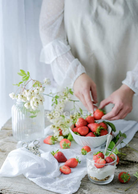 Creamy sweet dessert with fresh juicy strawberries served in glass on rustic wooden table with biscuits and female hand taking berries on background — Stock Photo