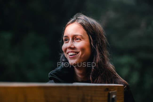 Mujer joven sonriente de pie contra el telón de fondo del río de montaña - foto de stock