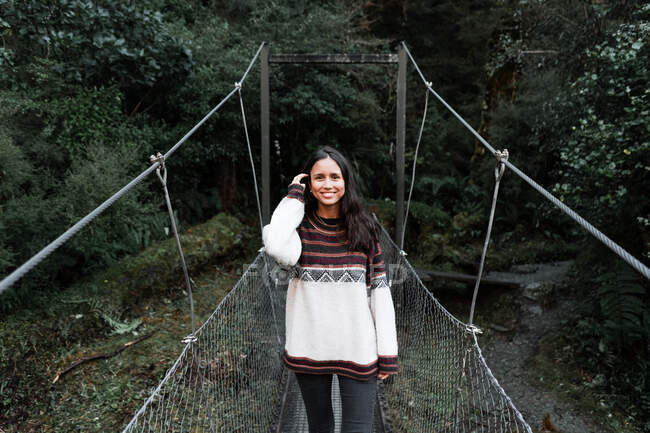 Giovane donna allegra in piedi sul ponte nella foresta — Foto stock