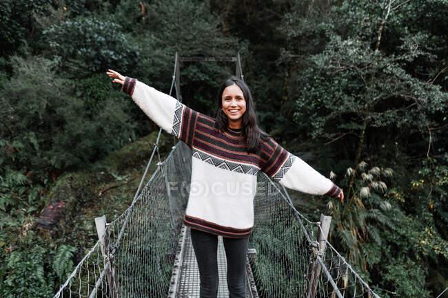 Jovem alegre em pé na ponte na floresta — Fotografia de Stock