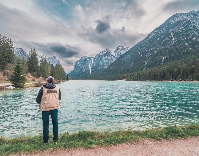 Vue arrière du mâle avec sac à dos debout sur la rive du lac et la pêche par une journée ensoleillée dans la nature — Photo de stock