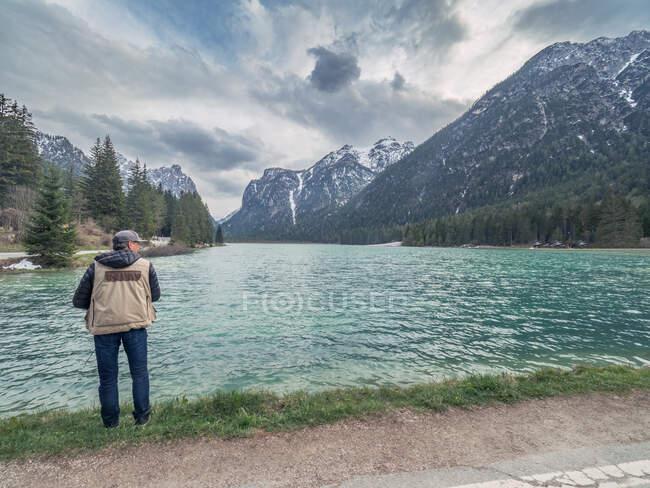 Vue arrière du voyageur adulte prenant des photos de la crête de montagne tout en se tenant sur la rive d'un lac calme dans la nature — Photo de stock