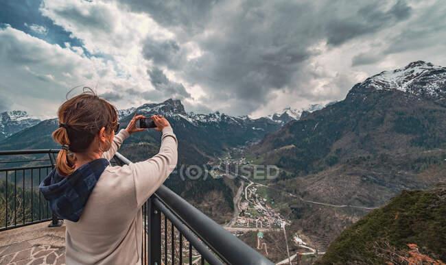 Задний вид женщины в теплой одежде, стоящей на пирсе и смотрящей на горный хребет и фотографирующей с мобильного телефона в сельской местности — стоковое фото
