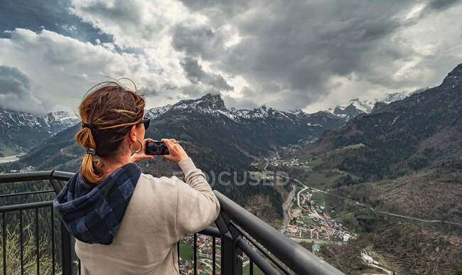 Back view woman in warm clothes standing on pier and looking at mountain ridge and taking picture with mobile phone in countryside — Stock Photo
