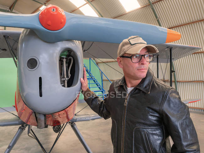 Confident pilot standing next to retro plane in hangar and looking away — Stock Photo