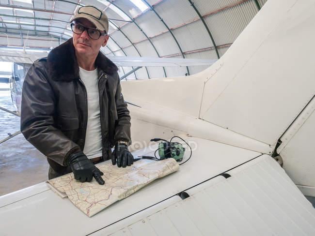Pilote avec carte debout près d'un petit avion et regardant loin — Photo de stock