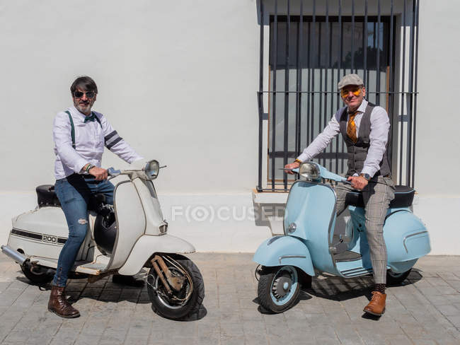 Positive middle-aged hipsters in elegant clothes with retro motorbikes looking at camera in sunny day — Stock Photo