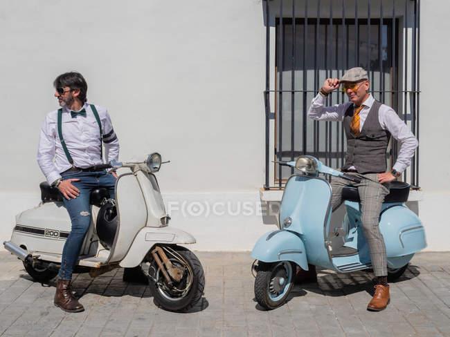 Positive Hipster mittleren Alters in eleganter Kleidung mit Retro-Motorrädern, die bei sonnigem Wetter wegschauen — Stockfoto