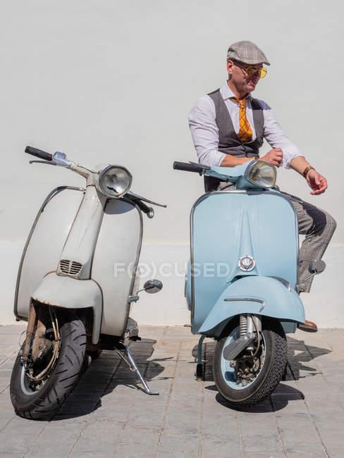 Positiver Hipster mittleren Alters in eleganter Kleidung mit Retro-Motorrädern, die bei sonnigem Wetter wegschauen — Stockfoto