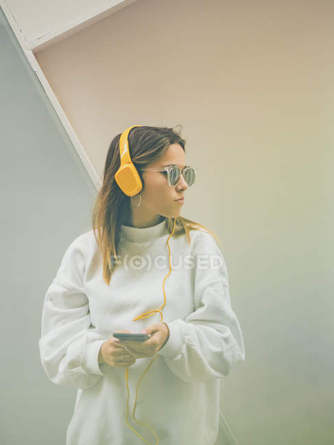 Confiado hipster femenino moderno en ropa casual usando auriculares de color amarillo brillante y teléfono inteligente en el fondo de la pared - foto de stock