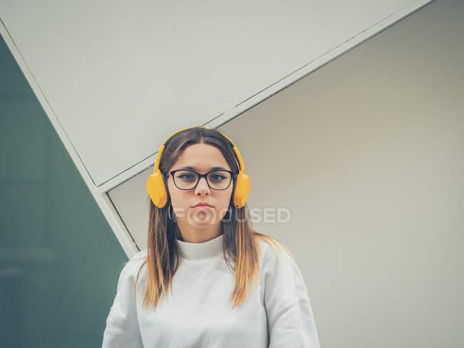 Confiado hipster femenino moderno en ropa casual y auriculares de color amarillo brillante en el fondo de la pared - foto de stock