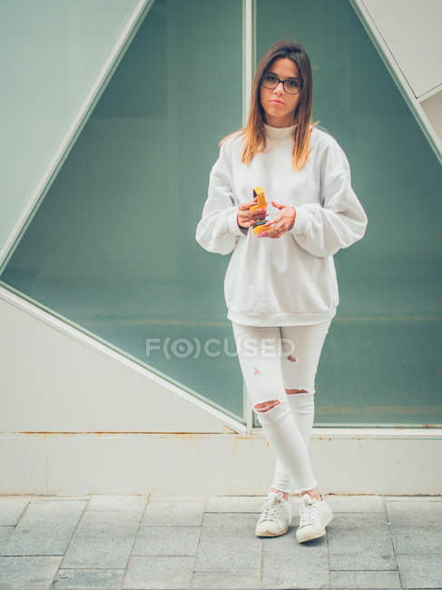 Young dreamy modern female hipster in casual white clothes holding bright yellow headphones on background of wall — Stock Photo