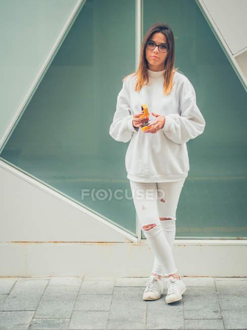 Молода мрійлива сучасна жіноча хіпстера в повсякденний білий одяг тримає яскраво-жовті навушники на тлі стіни — стокове фото