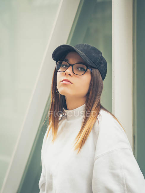 Young modern female hipster in casual clothes on background of geometric wall looking at camera — Stock Photo
