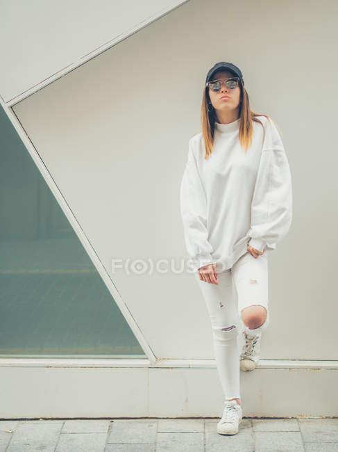 Joven hipster femenino moderno en ropa casual y gafas de sol sobre fondo de pared geométrica mirando a la cámara - foto de stock