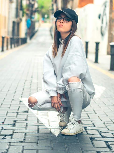 Giovane modello femminile moderno in eleganti vestiti casual sullo sfondo della strada estiva guardando la fotocamera — Foto stock
