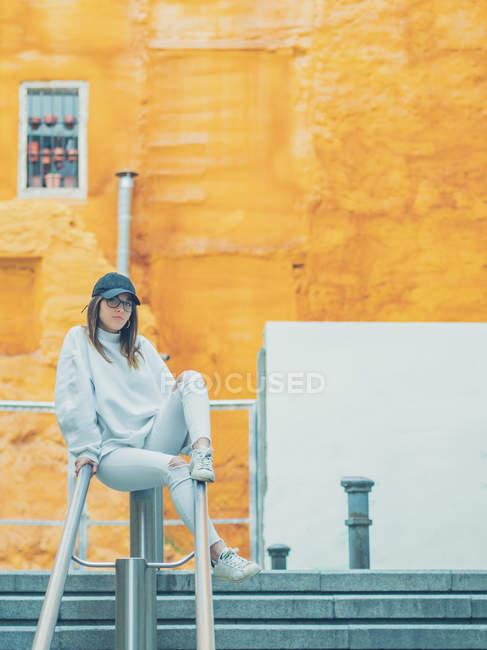 Joven chica femenina moderna en ropa casual con estilo sobre fondo naranja apoyada en la cerca - foto de stock