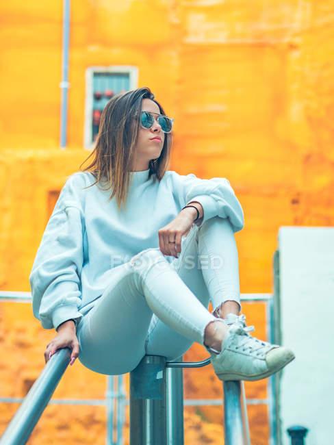 Modelo femenino moderno joven en ropa casual con estilo sobre fondo naranja apoyado en la valla - foto de stock