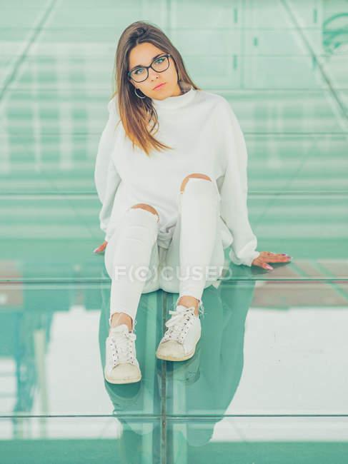 Joven hipster femenino moderno en ropa casual sobre fondo de gafas geométricas mirando a la cámara - foto de stock