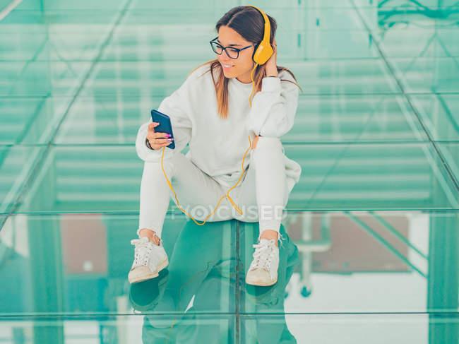 Joven hipster femenino moderno en ropa casual sobre fondo de gafas geométricas escuchando música con smartphone y mirando hacia otro lado - foto de stock