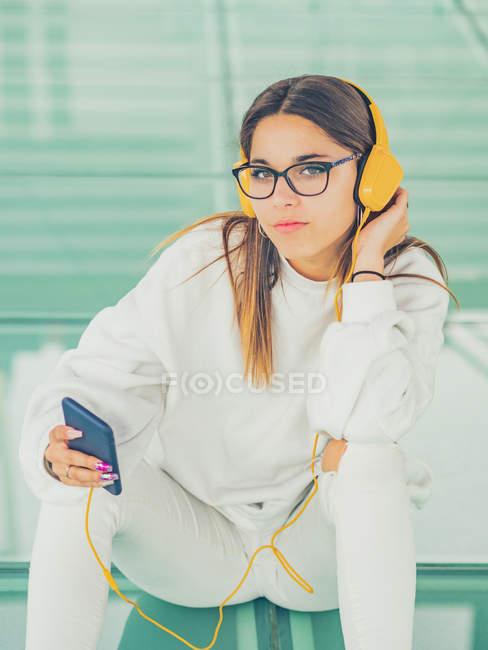 Joven hipster femenino moderno en ropa casual sobre fondo de gafas geométricas escuchando música con smartphone y mirando a la cámara - foto de stock