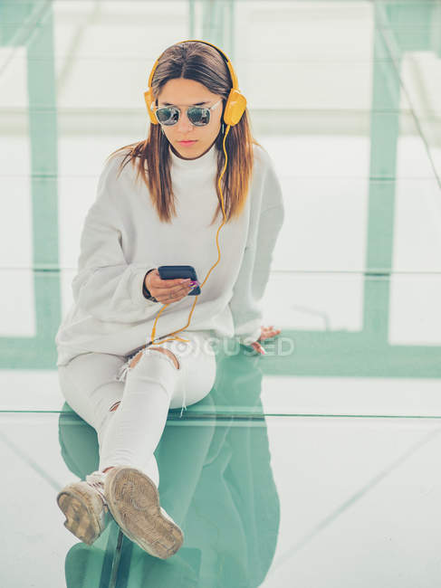 Joven hipster femenino moderno en ropa casual sobre fondo de gafas geométricas escuchando música con smartphone - foto de stock