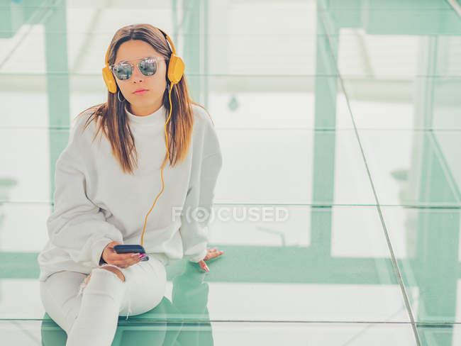 Joven moderna mujer hipster en ropa casual sobre el fondo de gafas geométricas escuchando música con teléfono inteligente - foto de stock